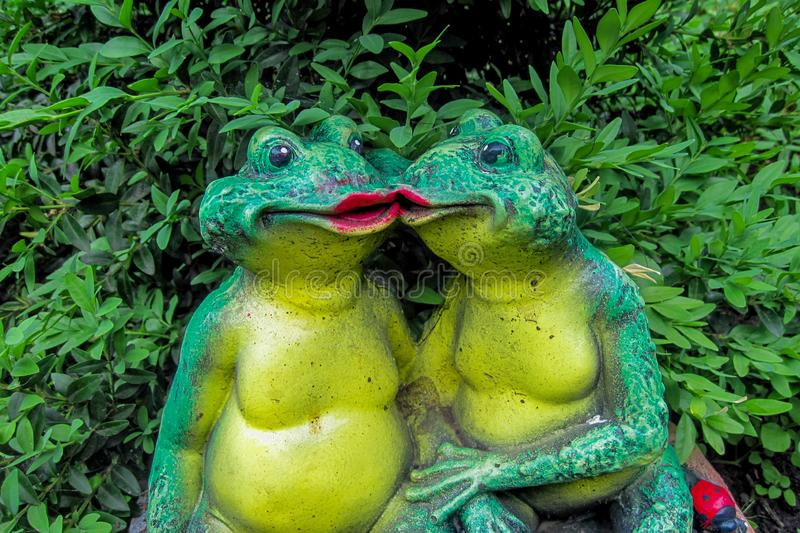 Two kissing frogs decor sculpture in garden backyard. Love story concept. Green toads in front of leaves of bush or shrub stock photo