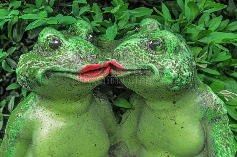 Two kissing frogs decor sculpture in garden backyard. Love story concept. Green toads in front of leaves of bush or shrub stock photos