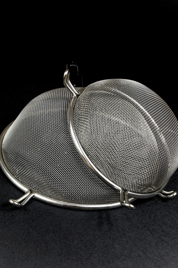 Two kitchen sieves on black background. Decoration royalty free stock image