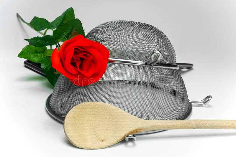 Two kitchen sieves with red rode and wooden spoon on black background. Decoration stock photography