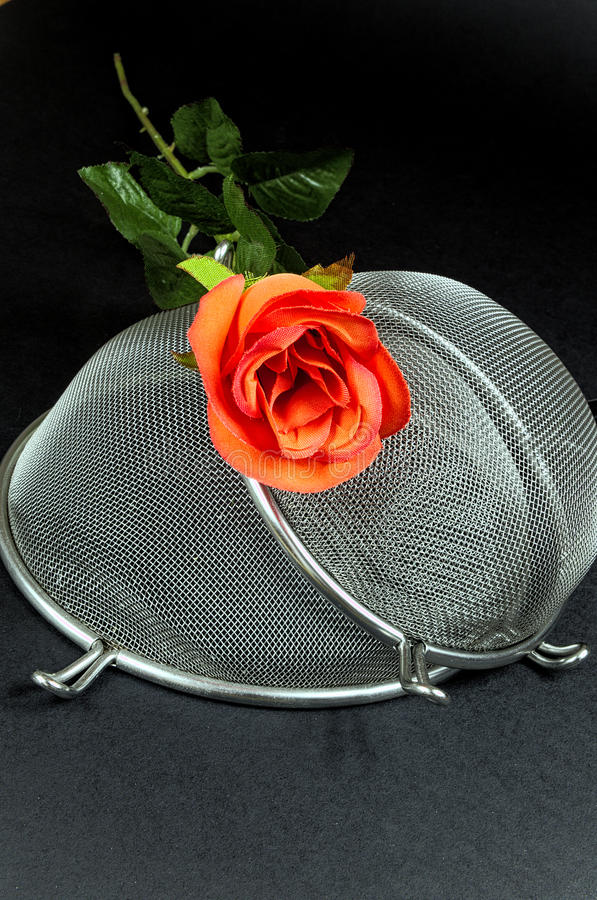 Two kitchen sieves with red rose on black background. Decoration stock photography