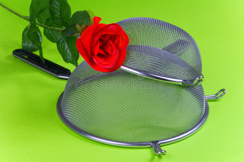 Two kitchen sieves with red rose and wooden spoon. On green background, decoration royalty free stock image