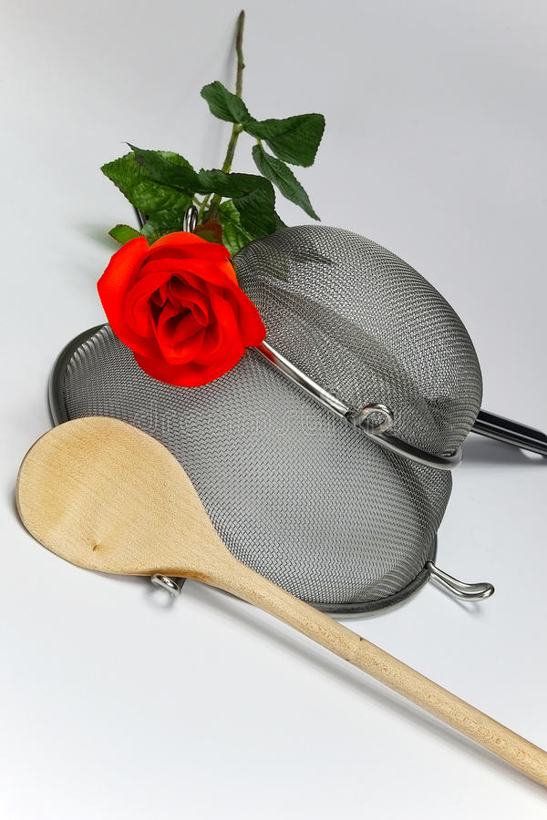 Two kitchen sieves with red rose and wooden spoon. On white background, decoration royalty free stock image