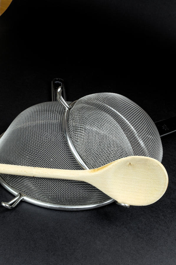 Two kitchen sieves with wooden spoon on black background. Decoration royalty free stock images