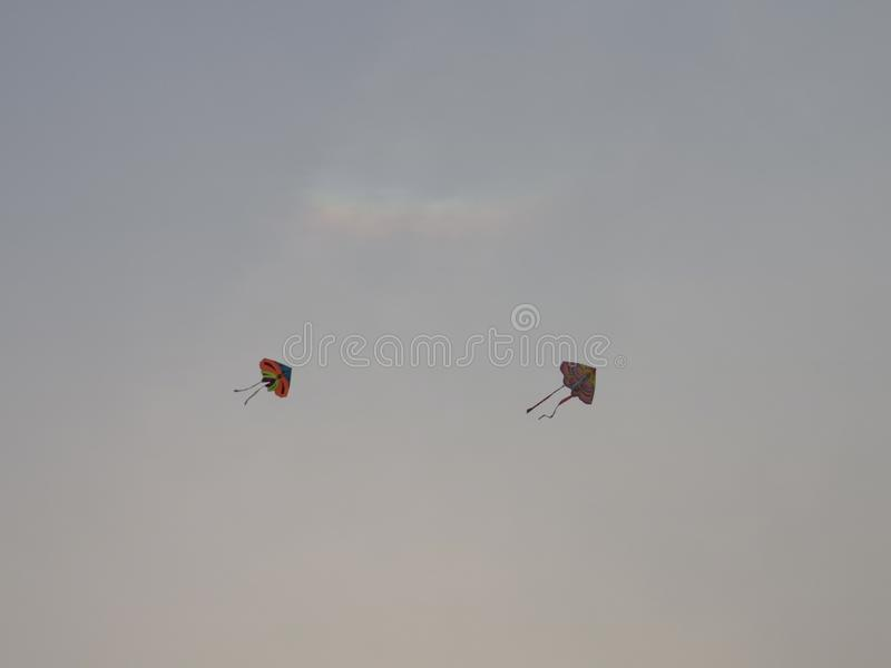 Two kites are flying in the sky during the time of sunsetting royalty free stock photos