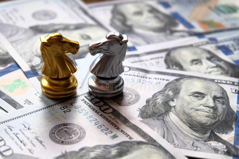 Two knights chess stand against each other on Us dollar banknote. Money game concept royalty free stock photo