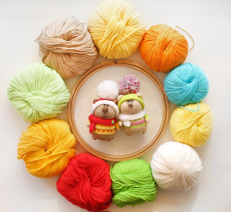 Two knitted bears in multicolored sweaters and hats with large pompoms on the background of colored balls of yarn. stock photo