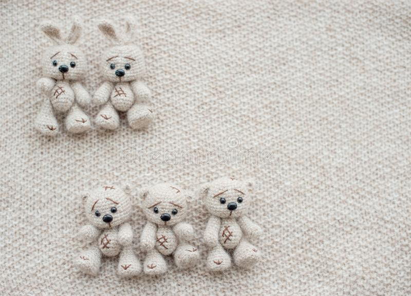 Two knitted white bunnies and three bears royalty free stock photos