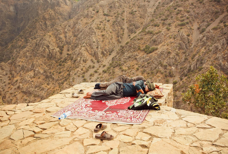 Two kurdish men sleeping over a precipice in mountaine village. HAWRAMAN, IRAN: Two kurdish men sleeping over a precipice in old mountaine village in Middle East royalty free stock photo