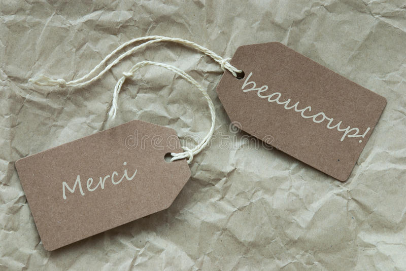 Two Labels Merci Beau Means Thank Paper Background. Two Beige Labels Or Tags With White Ribbon On Crumpled Paper Background With French Text Merci Beaucoup Means stock images
