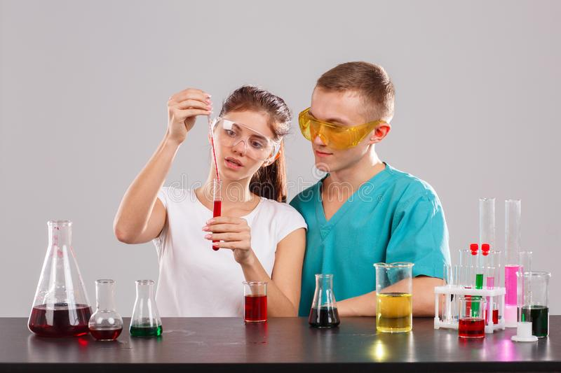 Two laboratory assistants, the girl pours a red liquid from a measuring pipette into a glass stake. Two young laboratory assistants in special glasses and stock images