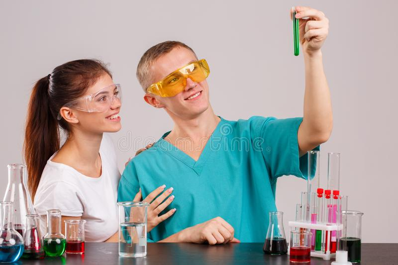 Two laboratory assistants. The guy is holding a flask with a green liquid and looking at it. Two laboratory assistants in uniform and special glasses. The guy royalty free stock photo