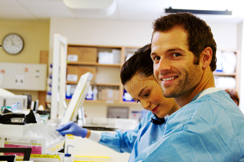 Two laboratory technicians working in hospital lab stock photography