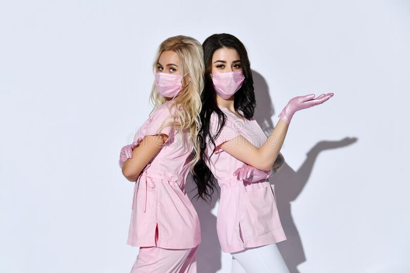 Two ladies in pink scrubs, disposable gloves and medical masks posing isolated on white. Medical staff, cosmetologist. Close up. Two ladies in pink scrubs stock image