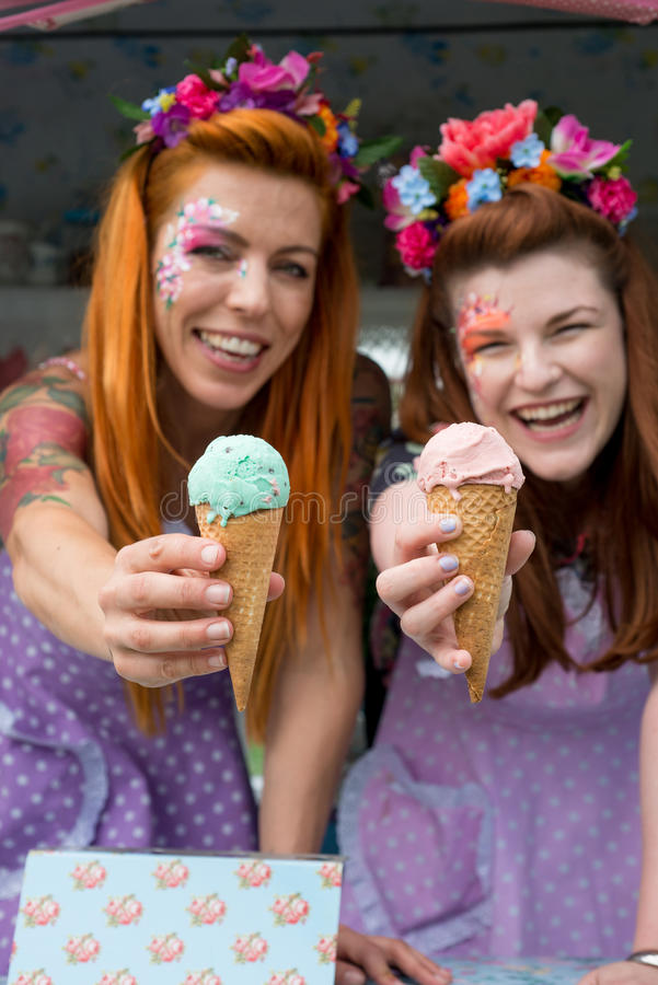 Two ladies wearing flower headbands holding ice cream from truck. Two ginger haired ladies smiling wearing flower headbands and vintage spotted dresses holding royalty free stock image