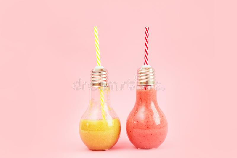 Two lamp- shaped jars with fruit smoothies isolated on pink background. stock photos