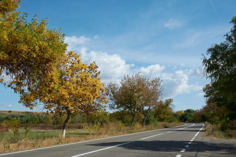 Two-lane asphalt country road, Landscape with view of non urban driveway, trees and blue sky with white clouds. Autumn landscape. On a sunny clear day royalty free stock photography