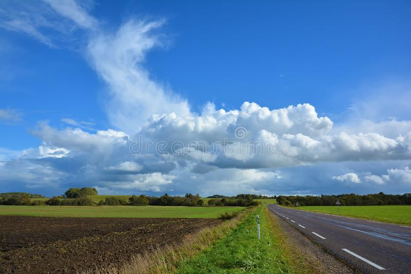 Two-lane asphalt country road, leaving beyond the horizon. Landscape with view of non urban driveway, green ..field, trees and. Blue sky with white clouds royalty free stock images