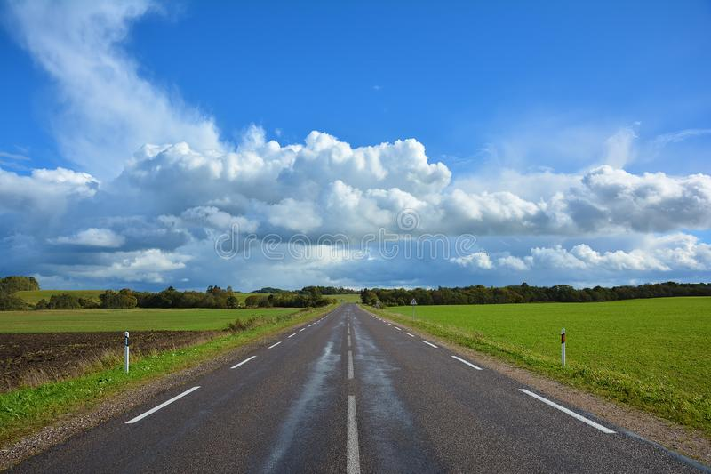 Two-lane asphalt country road, leaving beyond the horizon. Landscape with view of non urban driveway, green ..field, trees and. Blue sky with white clouds royalty free stock photo