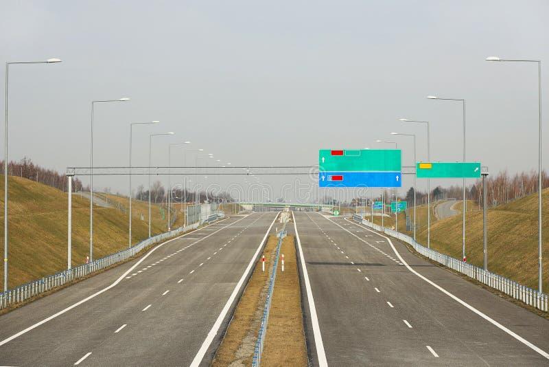 Two-lane autosnelweg met lege verkeersteken Nieuwe weg zonder auto's De ontwikkeling van vervoersinfrastructuur Landschapsontwerp royalty-vrije stock fotografie
