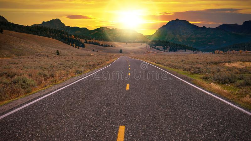 A two lane highway leading to a fresh new day. stock photo