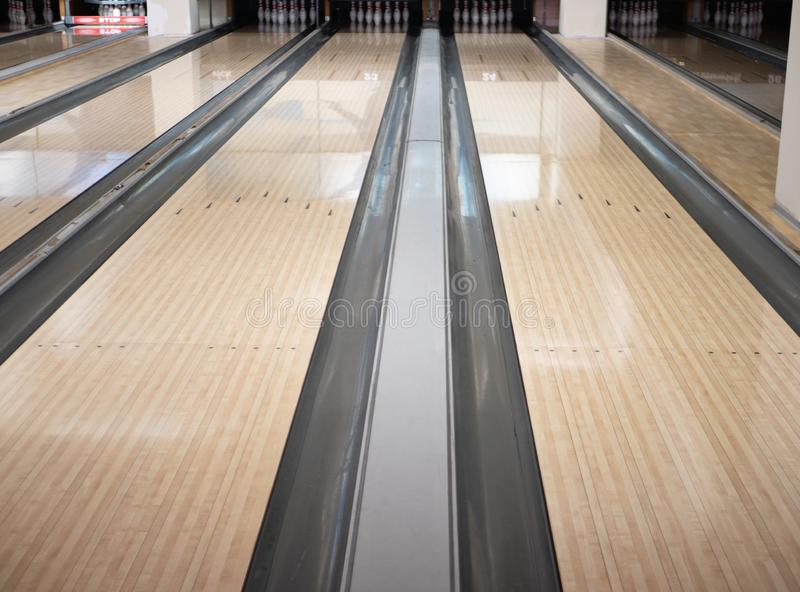 Two lanes tracks at bowling club with bunch of bowls pins at far distance. low angle image.  stock photos