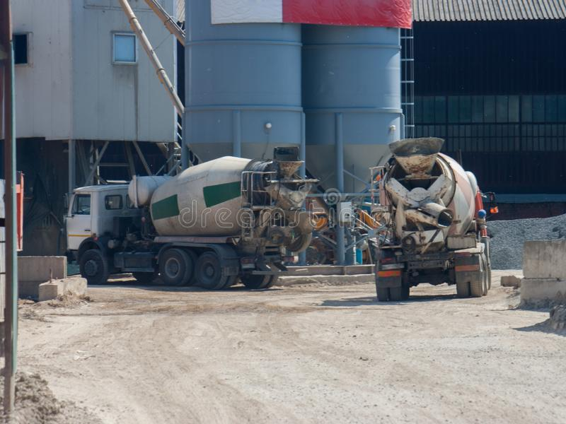 Two large cement truck trucks brought cement to the industrial area of the plant i. N special containers stock photo