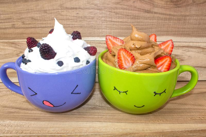 Two large mugs with painted faces, whipped cream and berries stand on a wooden shelf. Chocolate mousse with strawberries stock image