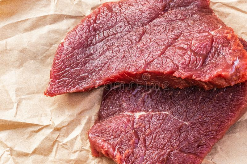 Two large raw beef steaks lie on food paper. Top view, close-up royalty free stock photography