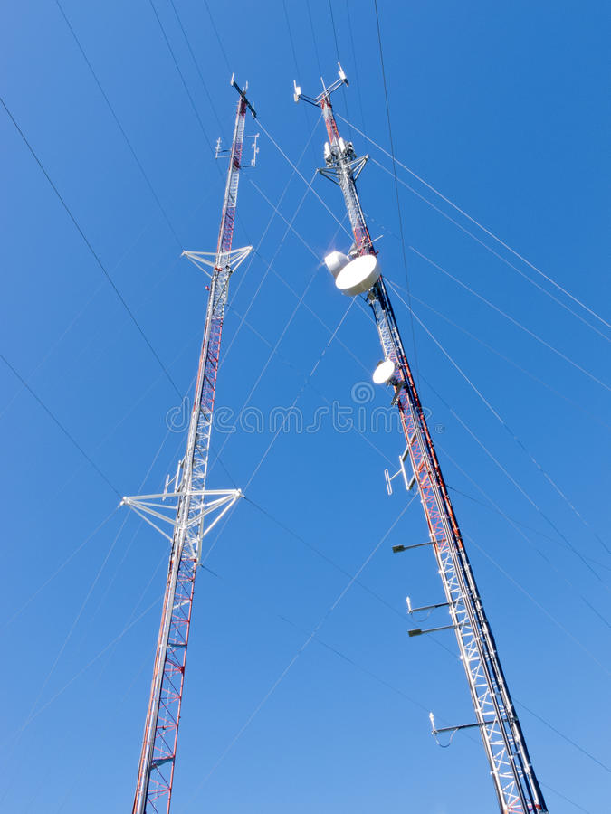 Two lattice telecommunication antenna towers. Two metal truss communication towers with various telecommunication antenna equipment, against clear blue sky, shot stock photography