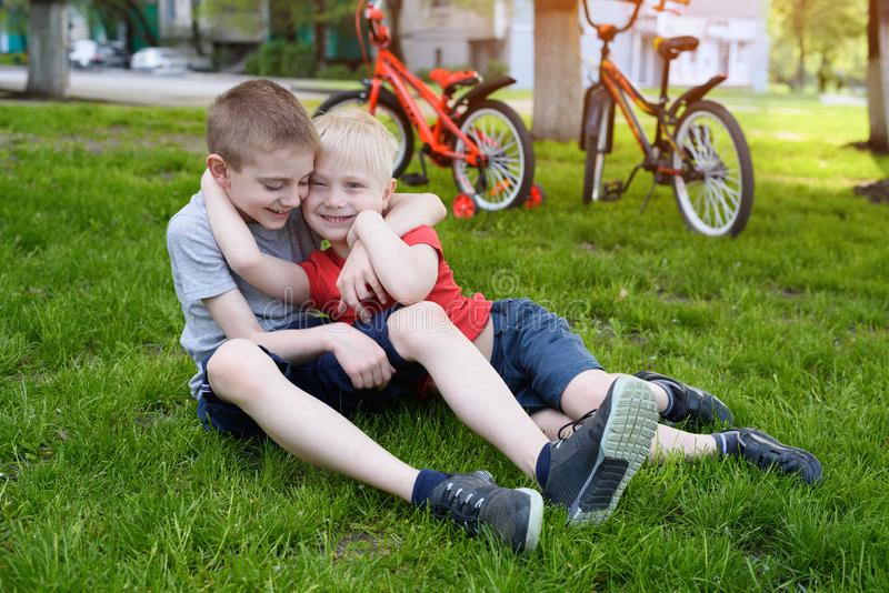 Two laughing boys having fun on the grass. Bicycles in the background stock photography