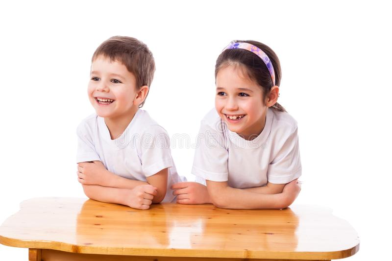 Two laughing kids at the desk looking aside stock photo