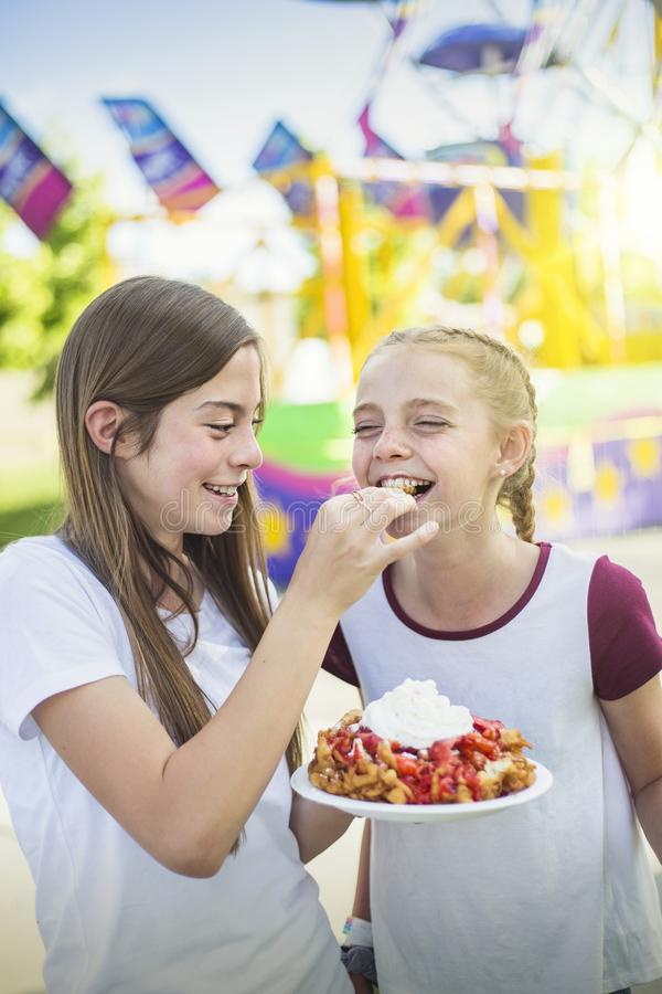 Two laughing teenage girls eating a funnel cake and whipped cream royalty free stock images