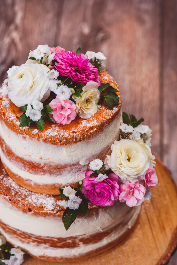 Two layered homemade cake. Closup shot of a two layered homemade naked cake decorated with flowers on wooden cut stand stock photo