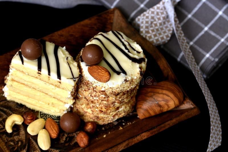 Two layered white chocolate and nuts keto desserts. Served on dark wooden tray, decorated with almonds and various nuts. Alternative ketogenic diet concept royalty free stock image