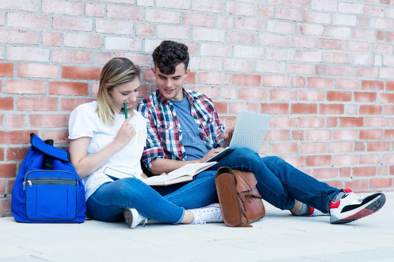 Two learning german students with book and laptop royalty free stock photos