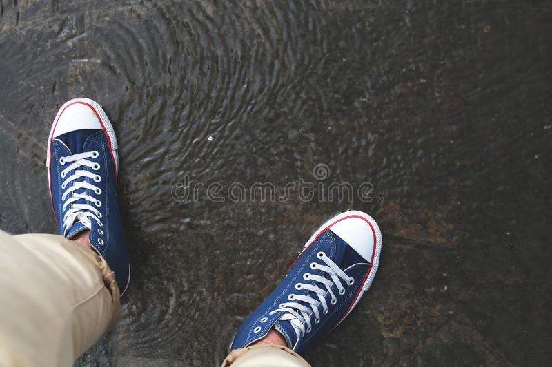 Two legs with wet shoes standing on the puddle after rain royalty free stock photo