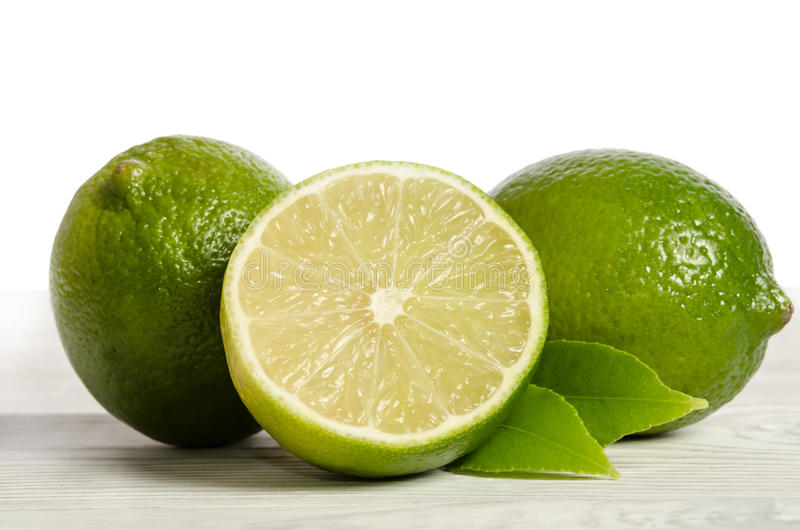 Two lemons with half of juicy lime on wooden table royalty free stock photo