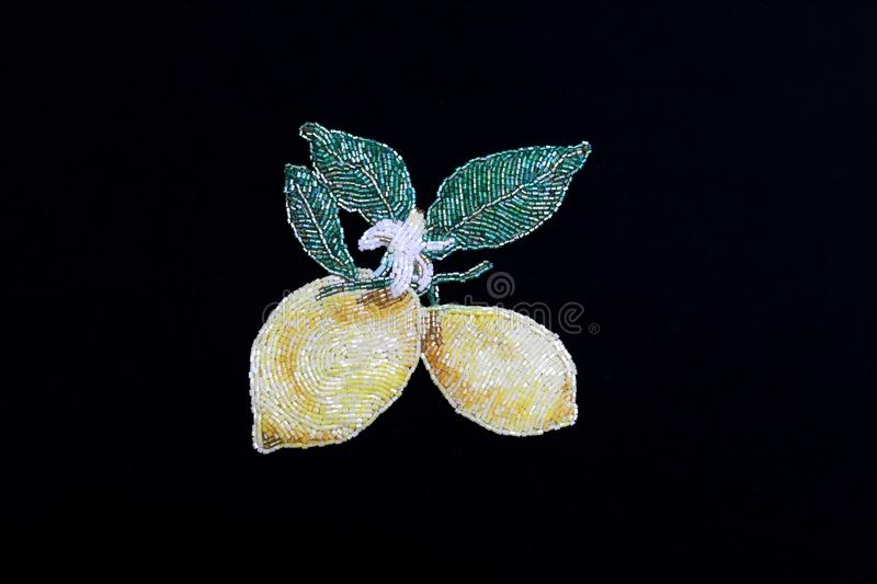 Designer brooch made of handmade bijouterie in the form of two lemons on a twig with three green leaves a branch isolated on a bla royalty free stock photo
