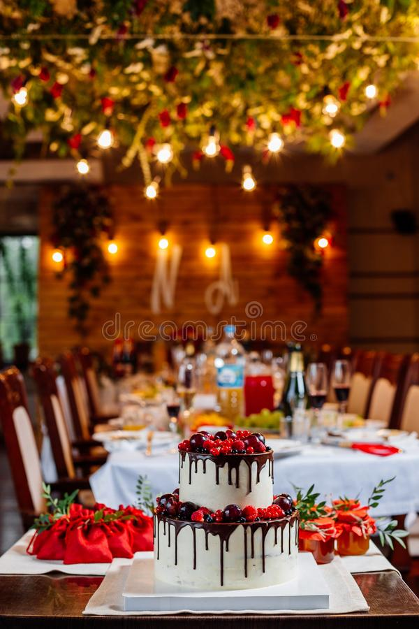Two level white wedding cake, decorated with fresh red fruits and berries, drenched in chocolate. Bright banquet table decoration. On background of lights and stock photo