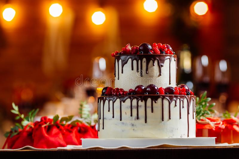 Two level white wedding cake, decorated with fresh red fruits and berries, drenched in chocolate. Bright banquet table decoration royalty free stock photos