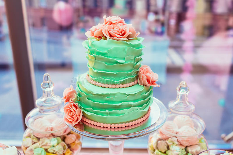 Two-leveled mint colored wedding cake with cream roses and macarons on background of glass showcase stock images