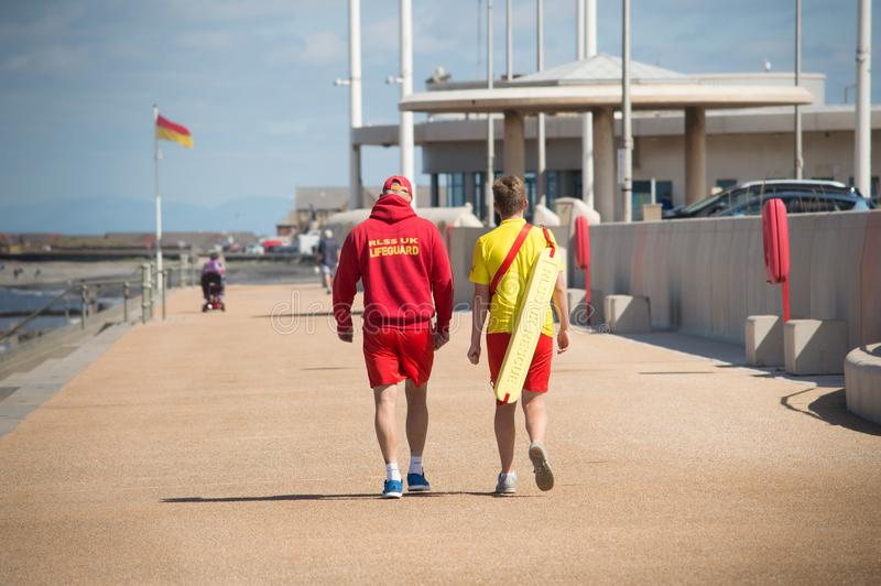 Two lifeguards walking in the sun stock photos