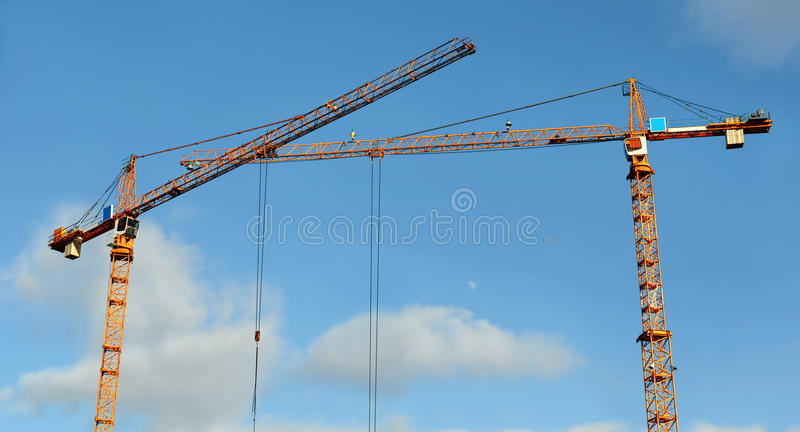 Two lifting tower cranes. Top parts of two orange lifting tower cranes with the crossed booms against the clear blue sky royalty free stock photo
