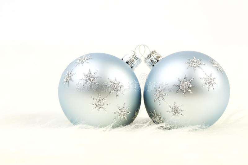 Two light blue and silver christmas balls on white fur background royalty free stock photography