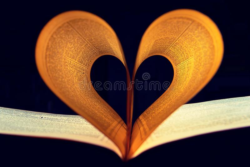 Two Lighted Pages of Book Formed Into Heart Shape Inside a Dark Room royalty free stock photo