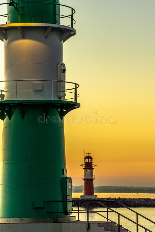Two lighthouses at beautiful sunset one green and the other red. Two lighthouses in beautiful sunset one green and the other red. Harbor entrance stock photo