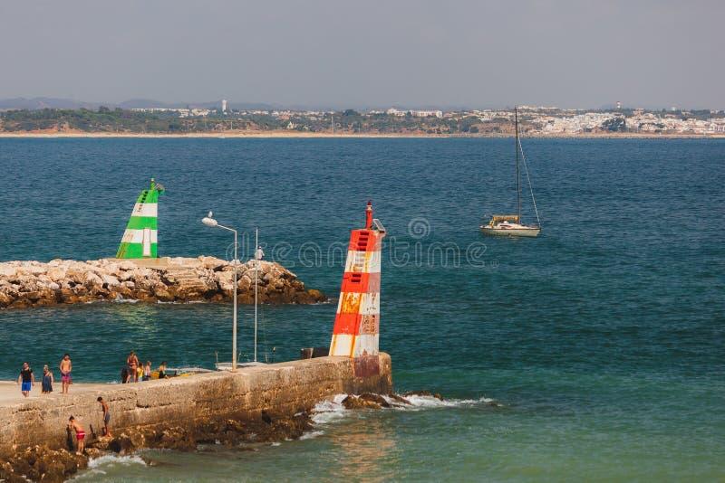 Two lighthouses, green, red, and white stripes at Praia da Batata, Lagos, Portugal. Two lighthouses, green, red, and white stripes. Beautiful Summer day at Praia stock photos