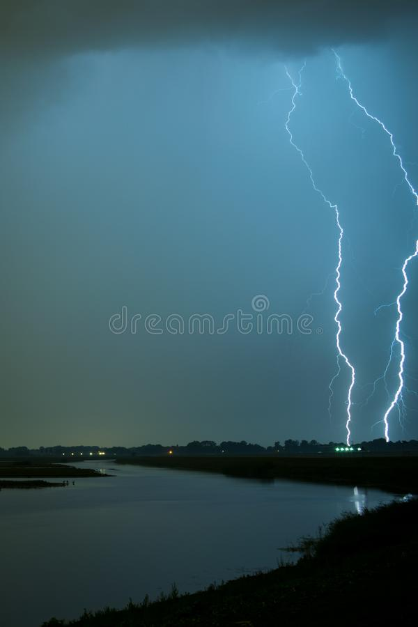 Two lightning bolts next to each other strike down to earth close to a lake near Rotterdam, The Netherlands. royalty free stock photos