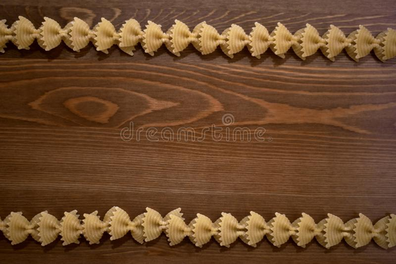 Two lines of pasta bows on a wooden background. stock photography